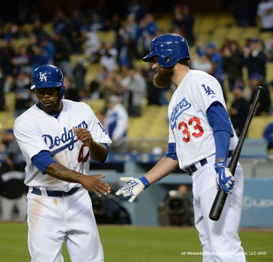Howie Kendrick is greeted by Scott Van Slyke at home plate after scoring in a run. Jill Weisleder/LA Dodgers