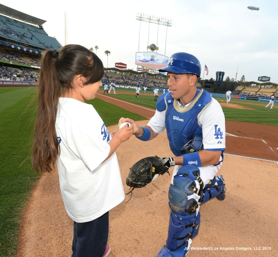A.J. Ellis signs a ball for a young fan participating during Kids Take The Field. Jill Weisleder/LA Dodgers