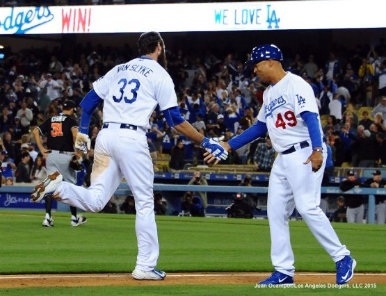Scott Van Slyke is congratulated by third-base coach Lorenzo Bundy.