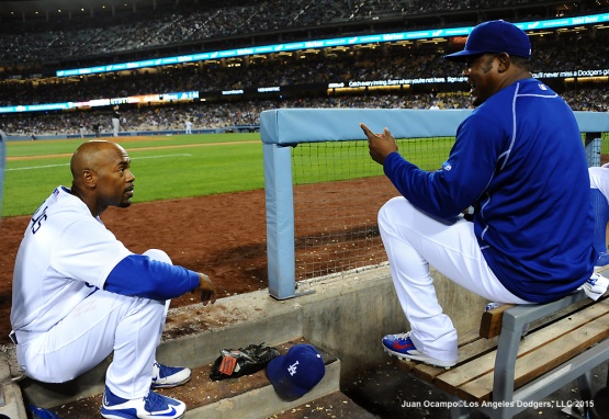 Jimmy Rollins and Juan Uribe talk in the dugout.