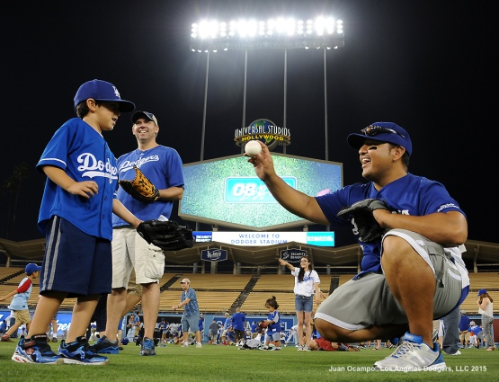 A father and son play catch on the Dodger Stadium outfield.