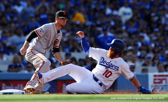 Justin Turner slides safely into third base ahead of the tag by the Giants' Matt Duffy in the first inning.