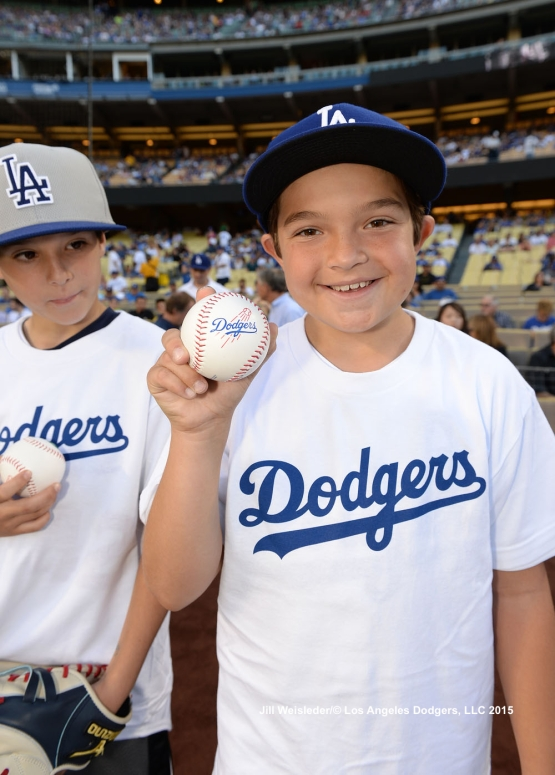A young participant shows off their baseball during Kids Take the Field. Jill Weisleder/LA Dodgers