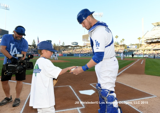 Yasmani Grandal signs a ball for a young participant during Kids Take the Field. Jill Weisleder/LA Dodgers