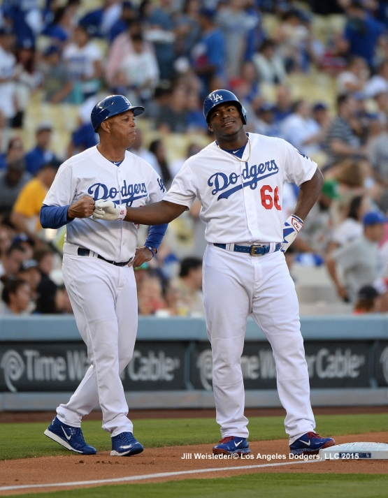 Third base coach Lorenzo Bundy bumps fists with Yasiel Puig after getting a triple. Jill Weisleder/LA Dodgers