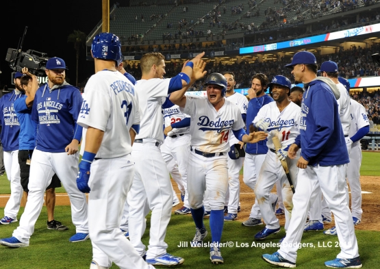 Enrique Hernandez is greeted by Dodger teammates as he comes in to score on walk-off balk by pitcher Keone Kela. Jill Weisleder/LA Dodgers