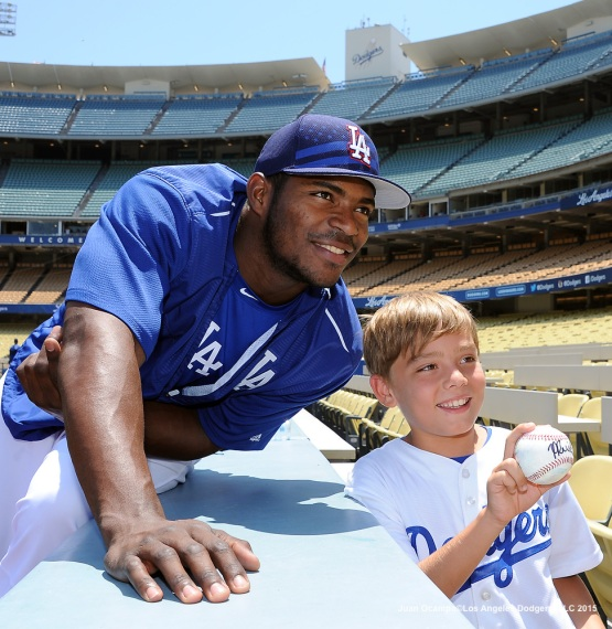 Yasiel Puig poses for a photo after autographing a young fan's baseball before the game.