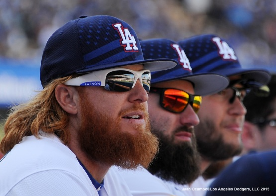 Justin Turner, Scott Van Slyke and Clayton Kershaw watch the game from the dugout.