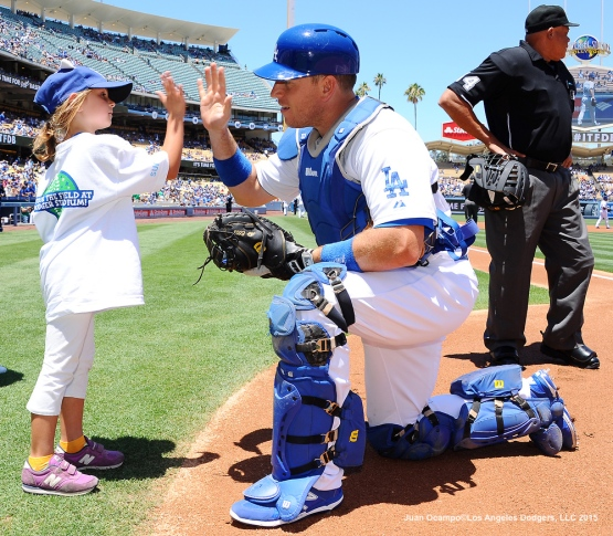 "A.J. Ellis high-fives a ""Kids Takes The Field"" participant."