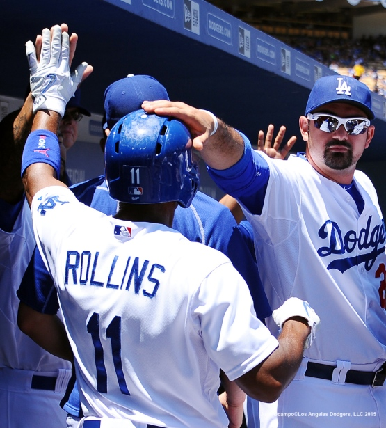 Adrian Gonzalez pats Jimmy Rollins on the helmet after Rollins scored in the first inning.