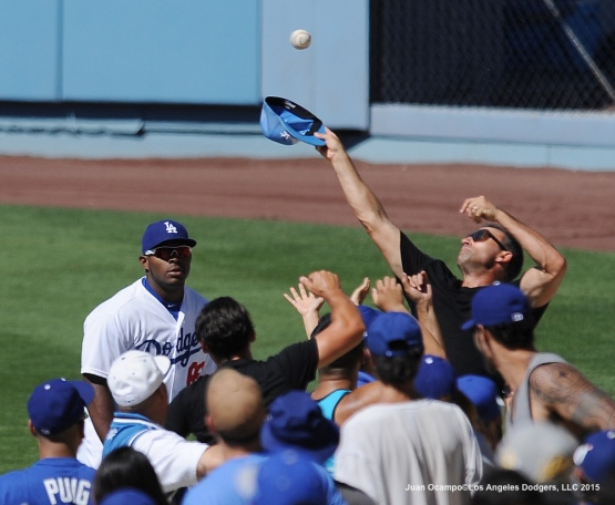 Yasiel Puig watches as fans try to catch a foul ball in the stands.