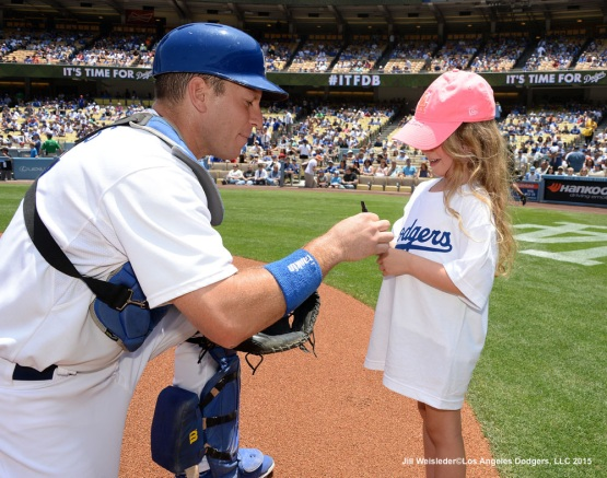Catcher A.J. Ellis signs a ball for a young fan during Kids Take The Field. Jill Weisleder/Dodgers