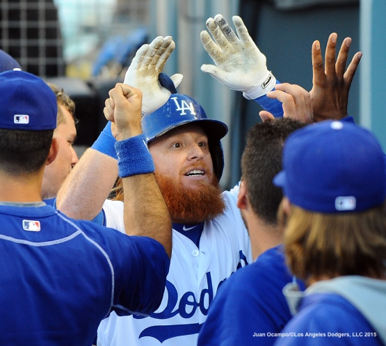Justin Turner high-fives his teammates in the dugout after his home run.