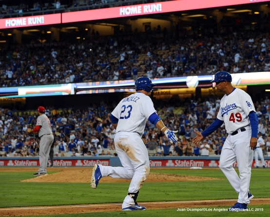 Adrian Gonzalez is congratulated by third base coach Lorenzo Bundy after his homer off of Reds reliever Pedro Villarreal in the fourth inning.