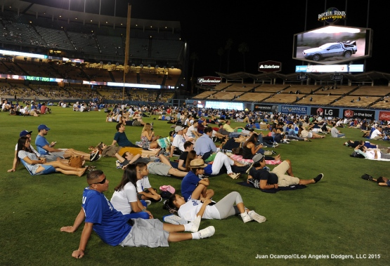 "Fans watch the movie, ""Back To The Future"" on the outfield grass after the game."