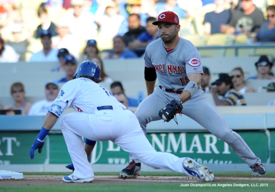 Kike Hernandez slides safely under the tag of Reds first baseman Joey Votto in the first inning.