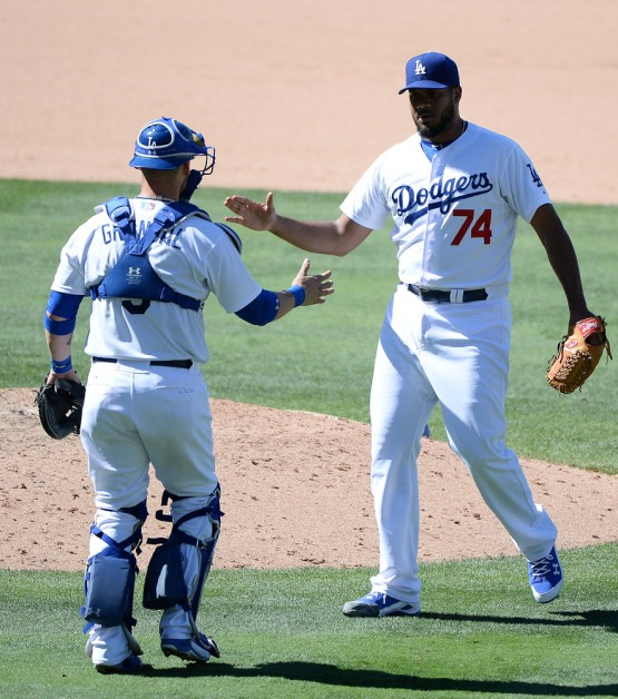 Kenley Jansen high-fives Yasmani Grandal after taking the win against the Reds 2-1. Jill Weisleder/LA Dodgers