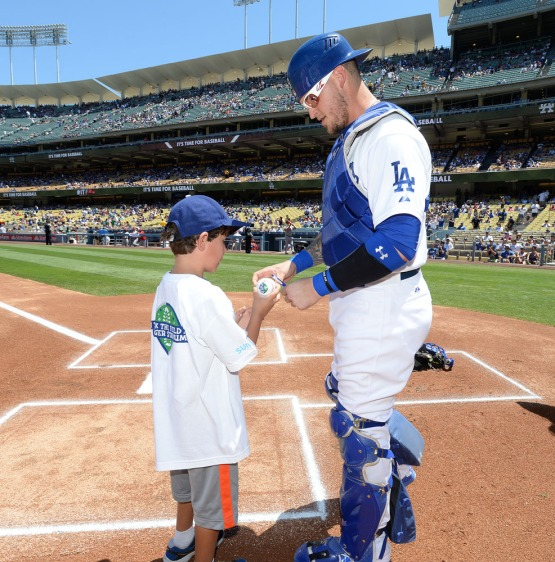 "Yasmani Grandal signs a ball for a fan during ""Kids Take the Field"". Jill Weisleder/LA Dodgers"