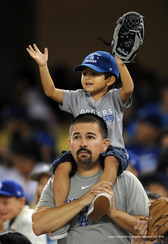 A father and son hope to catch a baseball during the game.