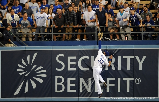 Scott Van Slyke leaps but is unable to make the catch in right field.