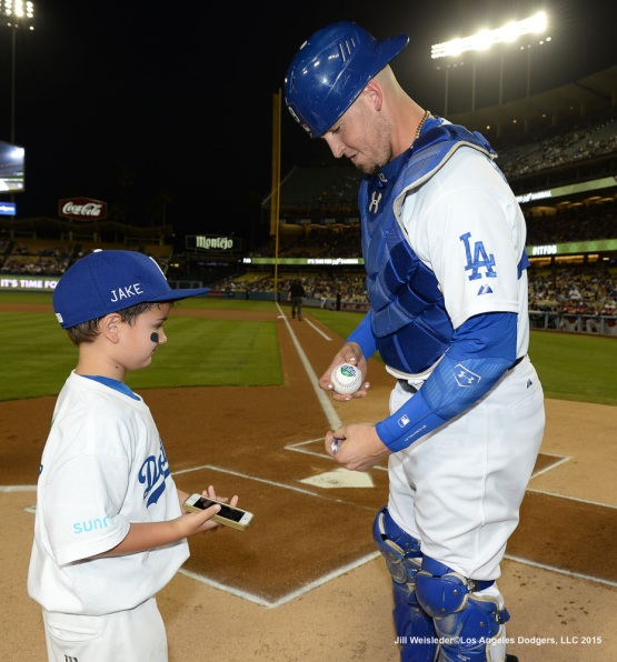 Yasmani Grandal signs a ball for a young fan. Jill Weisleder/LA Dodgers