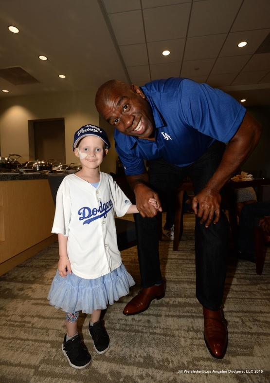 Ella Annear and Magic Johnson pose for a photo. Jill Weisleder/Dodgers