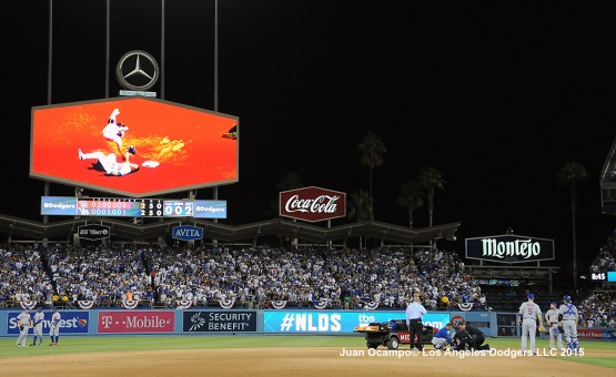 A cart is brought into the field to transport the Mets' Ruben Tejada as the replay is shown on the Dodgers DiamondVision board.