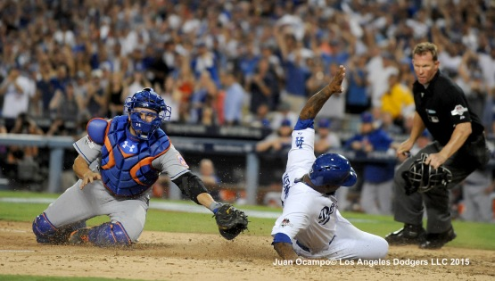 Howie Kendrick slides safely into home ahead of the tag by the Mets' Travis d'Arnaud.
