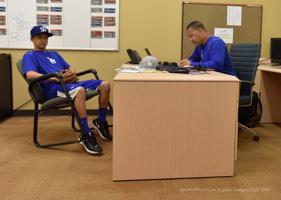 Los Angeles Dodgers Manager Dave Roberts behind his desk with son Cole during reporting day for pitchers and catchers Friday, February 19, 2016 at Camelback Ranch-Glendale in Phoenix, Arizona