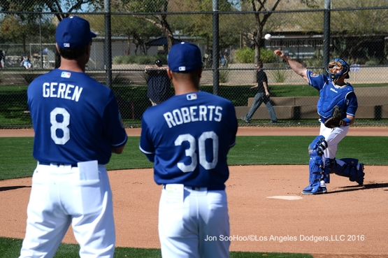 Los Angeles Dodgers Bob Geren and Dave Roberts watch A.J. Ellis throw during workout Wednesday, February 24,2016 at Camelback Ranch-Glendale in Phoenix, Arizona.