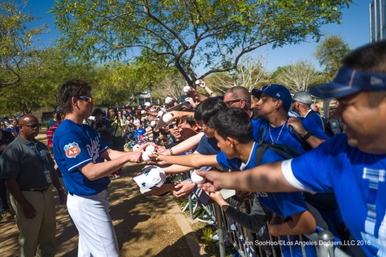 Los Angeles Dodgers Kenta Maeda signs for fans during workout Sunday, February 28, 2016 at Camelback Ranch-Glendale in Phoenix, Arizona.