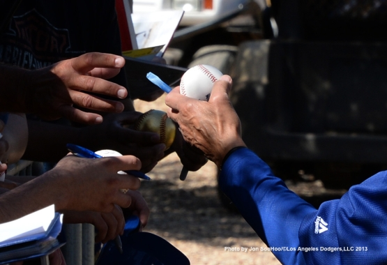 Los Angeles Dodgers Maury Wills hands ball to fan during first full squad workout Thursday, February 25, 2016 at Camelback Ranch-Glendale in Phoenix, Arizona.