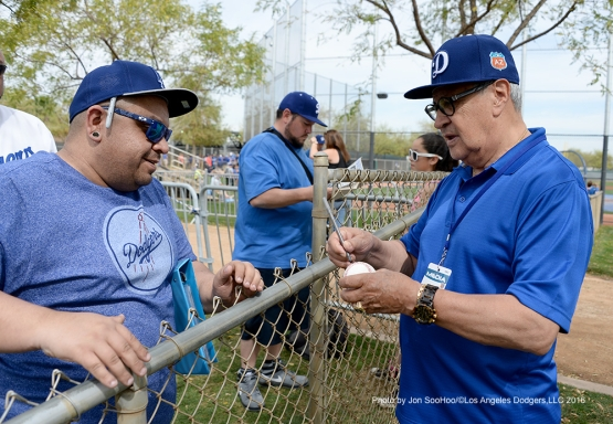 Los Angeles Dodgers Jaime Jarrin signs for fan during workout Thursday, March 3, 2016 at Camelback Ranch-Glendale in Phoenix, Arizona.