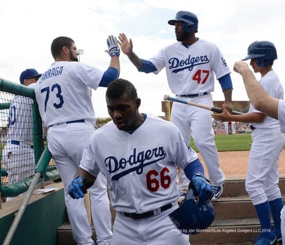 Los Angeles Dodgers Yasiel Puig and Howie Kendrick high five into the dugout during game against the Arizona Diamondbacks  Saturday, March 5, 2016 at Camelback Ranch-Glendale in Phoenix, Arizona.