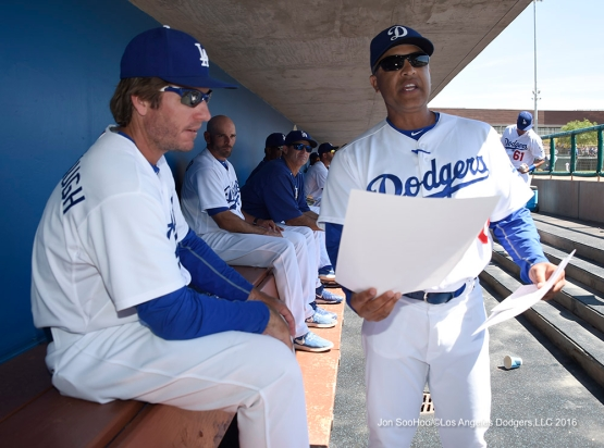 Los Angeles Dodgers Dave Roberts talks to bench coach Clayton McCullough during game against the San Diego Padres Sunday, March 20, 2016 at Camelback Ranch-Glendale in Phoenix, Arizona.