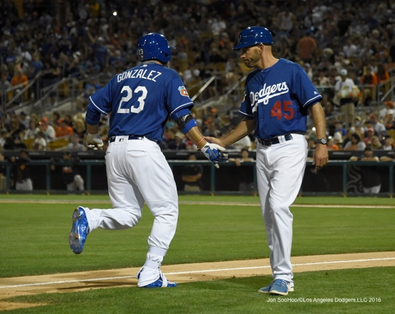 Los Angeles Dodgers Adrian Gonzalez is congratulated by third base coach Chris Woodward after home run during game against the San Francisco Giants Friday, March 25, 2016 at Camelback Ranch-Glendale in Phoenix, Arizona