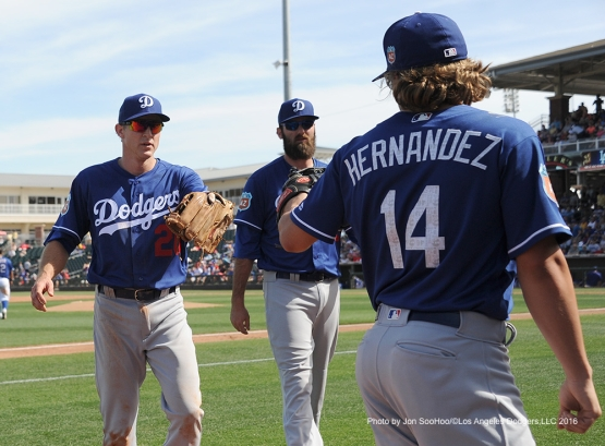 Los Angeles Dodgers Chase Utley, Scott Van Slyke are greeted by Kike Hernandez at the dugout during game against the Texas Rangers Friday, March 4, 2016 at Surprise Recreation Campus in Surprise, Arizona.