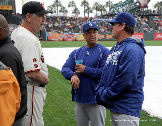 Los Angeles Dodgers Dave Roberts and Rick Honeycutt talk to  San Francisco Giants manager Bruce Bochy during rain delay Saturday, April 9, 2016 at AT&T Park in San Francisco,California. The Dodgers beat the Giants 3-2.