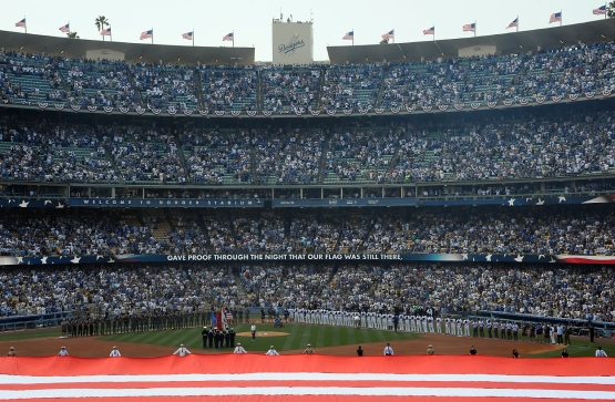 The Dodgers and Diamondbacks stand on the baselines during the national anthem.