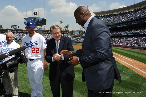 "Peter Omalley hands ball to Earvin ""Magic"" Johnson before game against the Arizona Diamondbacks Tuesday, April 12, 2016 at Dodger Stadium."