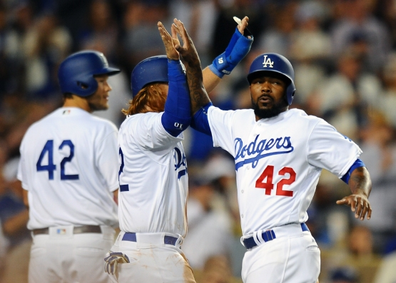 Howie Kendrick and Justin Turner high-five each other after both scoring in the fourth inning.