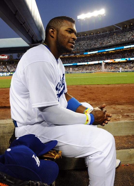 Yasiel Puig sits in the dugout.