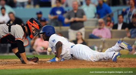 Yasiel Puig slides safely into home ahead of the throw to Giants catcher Buster Posey.