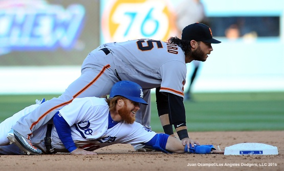 Justin Turner slides into Giants second baseman Brandon Crawford.