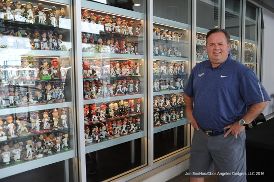 Clubhouse Manager Mitch Poole stands in front of his late collection of bobbleheads on display Tuesday, April 26, 2016 at Dodger Stadium.