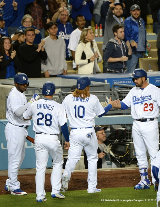Adrian Gonzalez high-fives Justin Turner and Austin Barnes as they come in to score in the seventh inning. Jill Weisleder/Dodgers