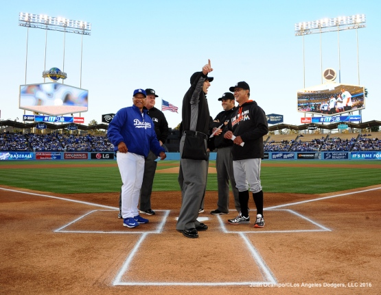 Dodgers manager Dave Roberts and Marlins manager Don Mattingly share a moment with the umpires before the game.