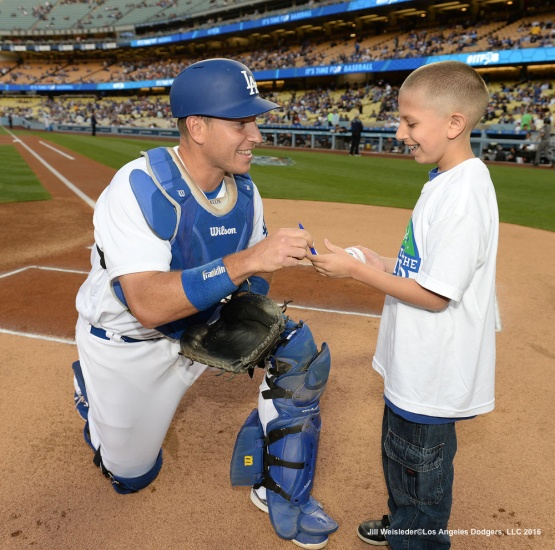 Dodger catcher A.J. Ellis signs a ball for a young fan during Kids Take the Field prior to the start of the Arizona Diamondbacks game. Jill Weisleder/Dodgers
