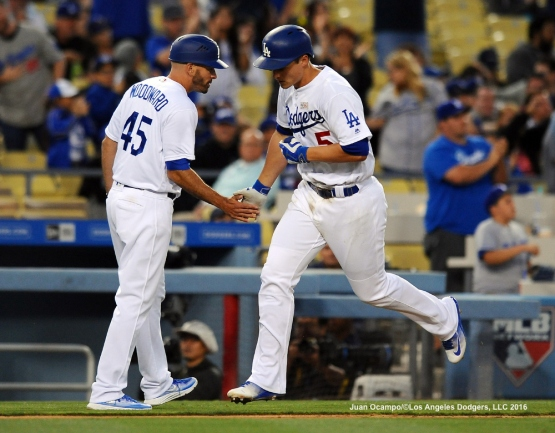 Corey Seager is congratulated by third base coach Chris Woodward.