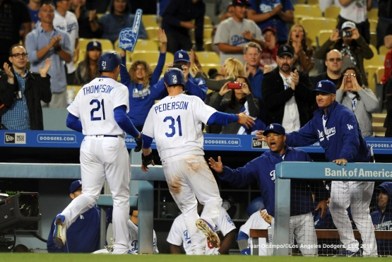 Trayce Thompson and Joc Pederson are greeted by manager Dave Roberts and coach Bob Geren in the dugout.
